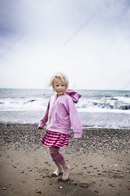 Girl walking barefoot on the beach