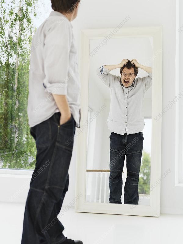 Man examining his grimacing reflection