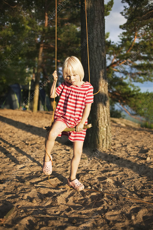 Girl playing on tree swing in forest