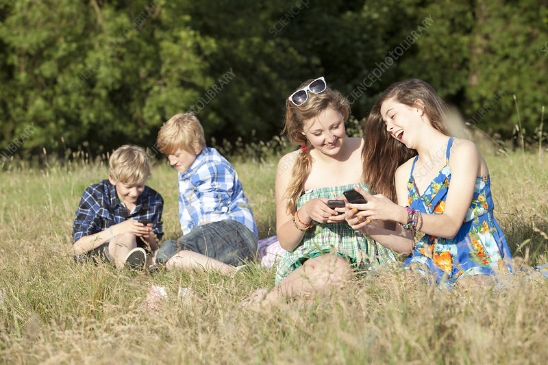 Children using cell phones in field