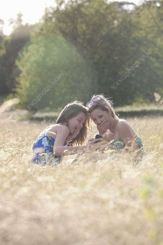 Laughing girls using cell phone in field