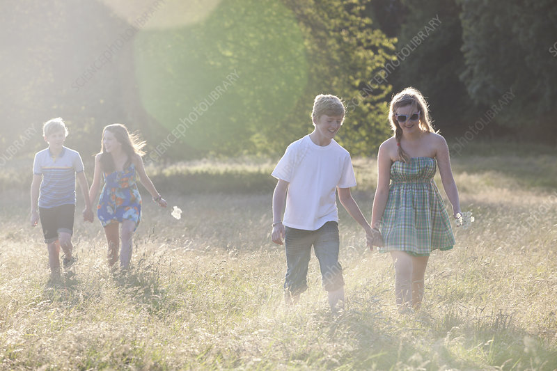 Teenage couples walking in field