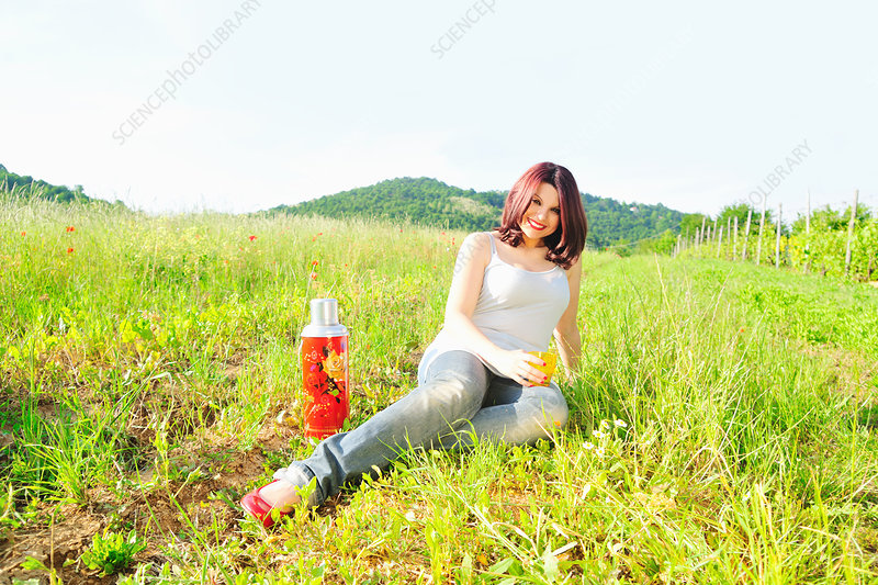 Woman drinking from thermos in field