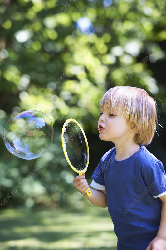 Boy blowing oversized bubble in backyard