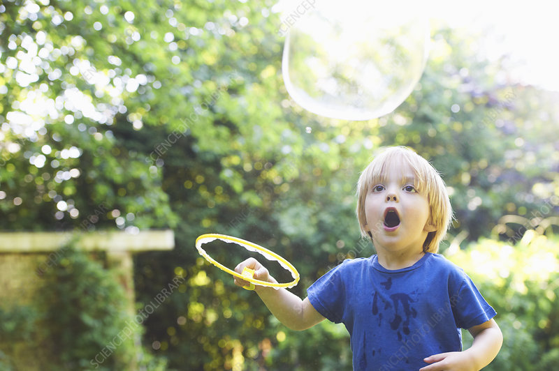 Boy making oversized bubble in backyard