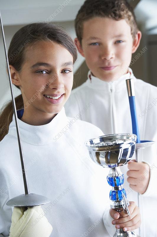Smiling girl holding fencing trophy