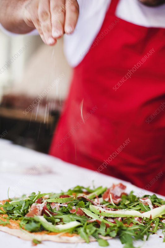 Chef sprinkling spices over pizza