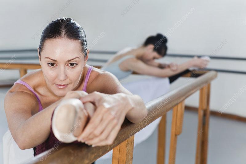 Ballet dancers stretching at barre