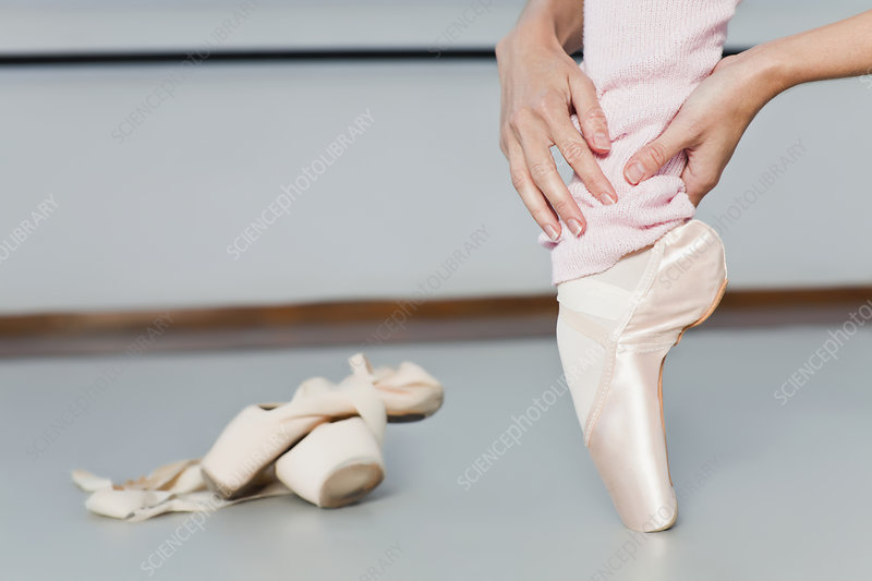Ballet dancer examining toes on pointe