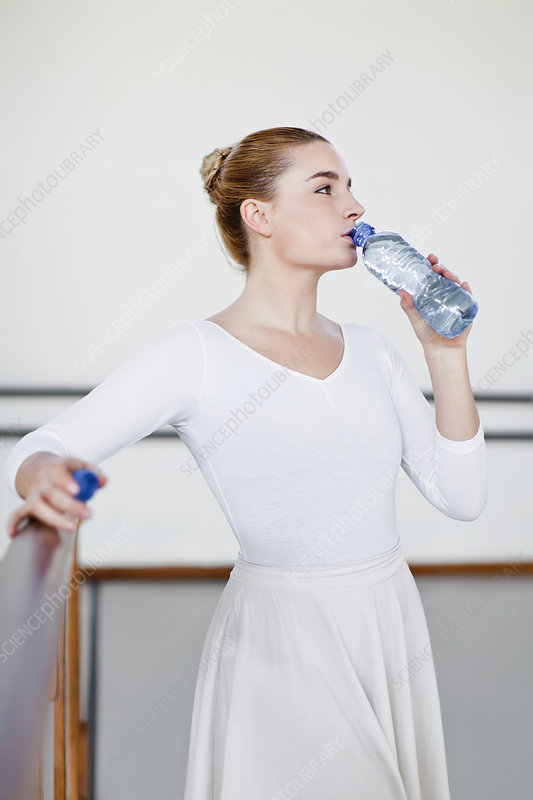 Ballet dancer drinking water in studio