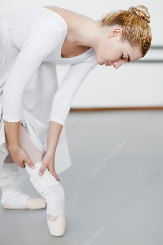 Ballet dancer examining hurt ankle