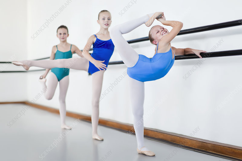Ballet dancers posing at barre