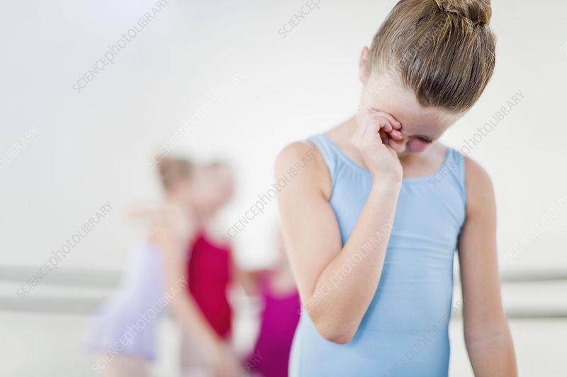 Ballet dancer wiping her eyes in studio