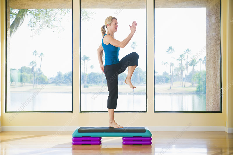 Woman practicing step aerobics in studio