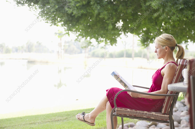 Woman reading magazine outdoors