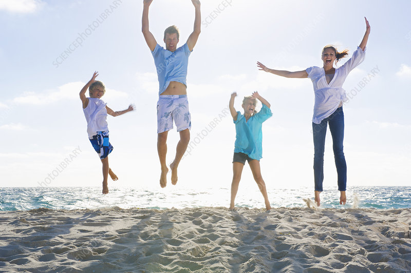 Family jumping together on beach