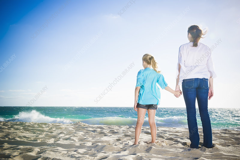 Mother and daughter standing on beach