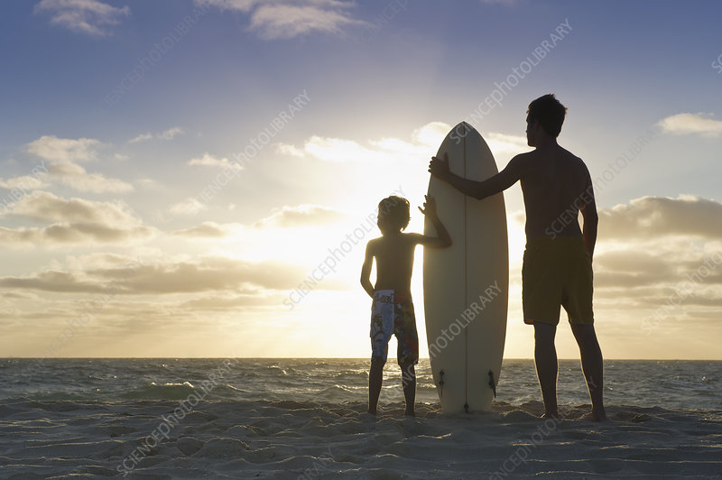 Father and son with surfboard on beach