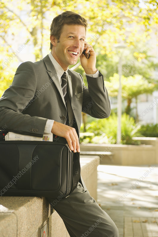 Businessman on cell phone in urban park