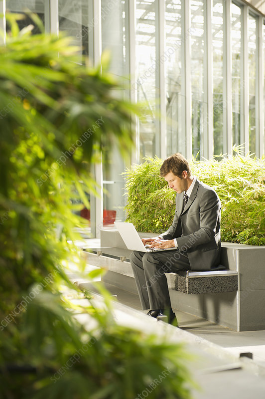 Businessman using laptop in urban park