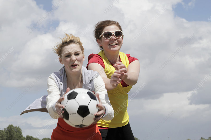 Girls playing soccer together