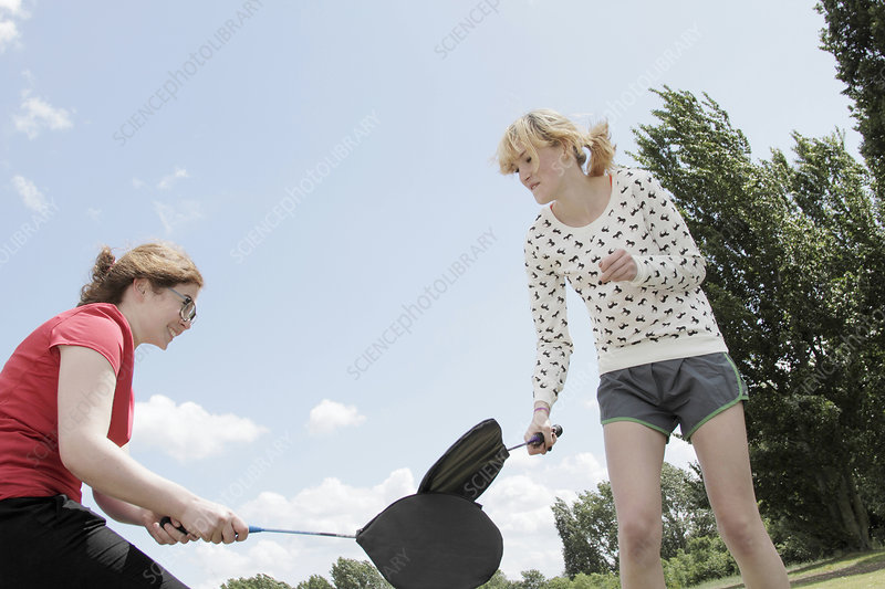 Girls playing with rackets in park