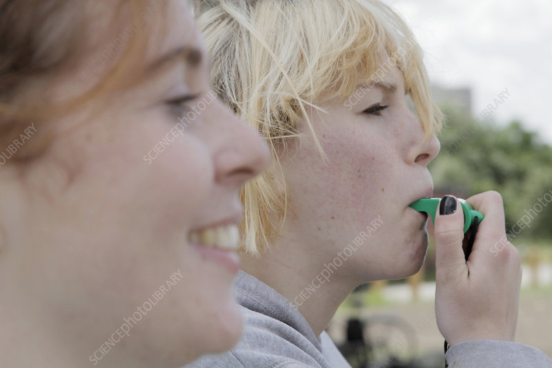 Girl blowing whistle outdoors
