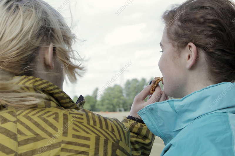 Girls sharing cookie outdoors