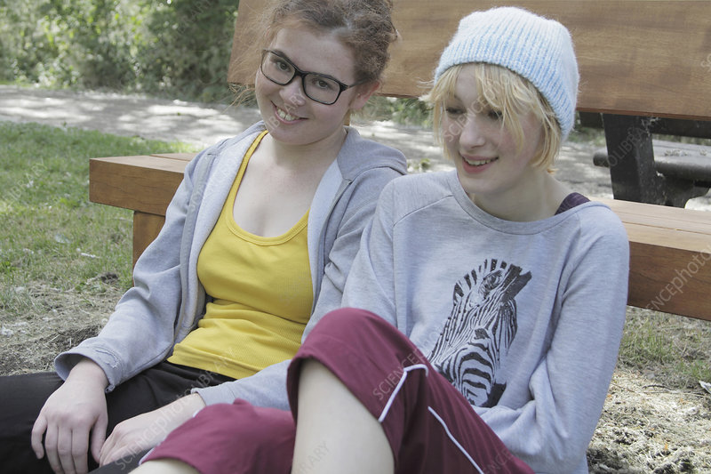 Girls leaning on park bench