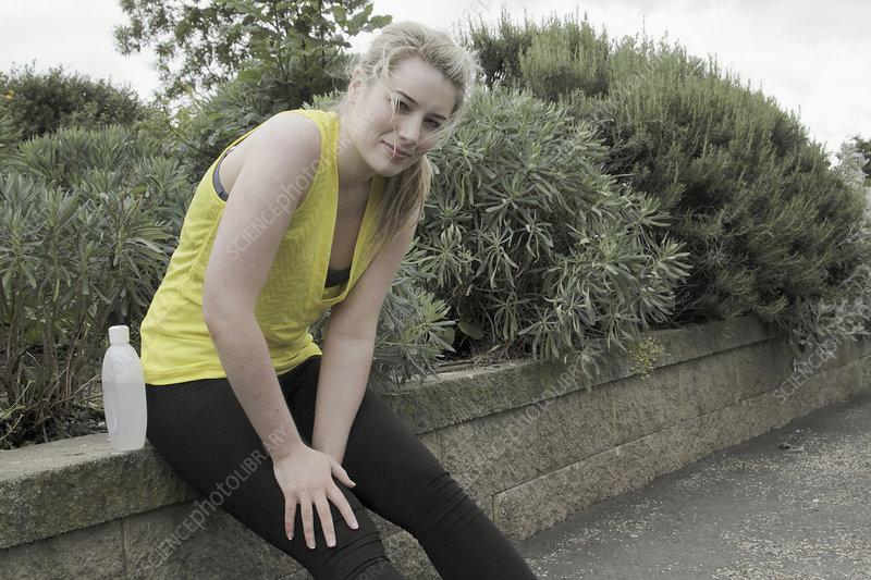 Runner resting on brick wall in park