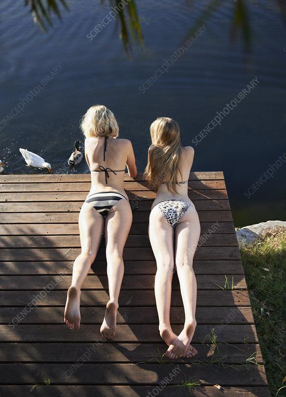 Women in bikinis laying on deck