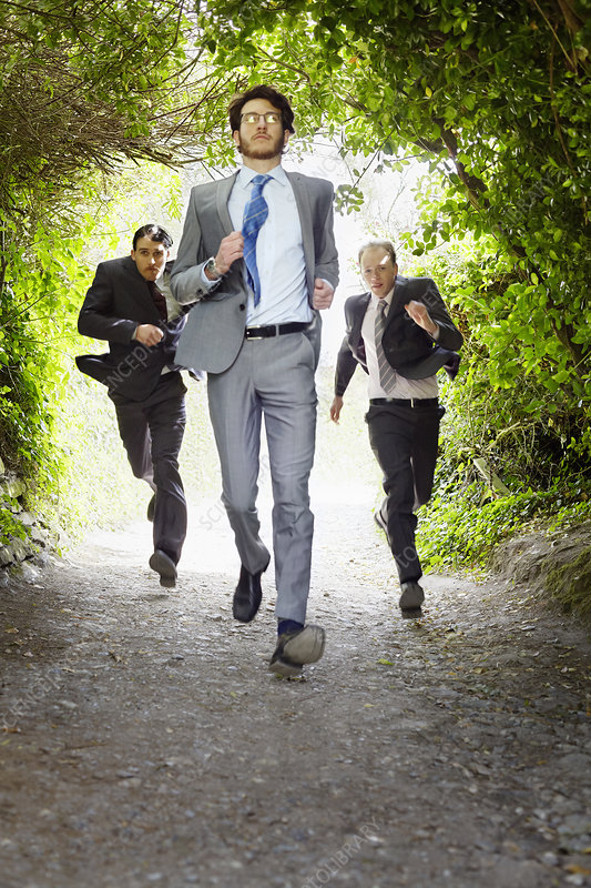 Businessmen running on rural road