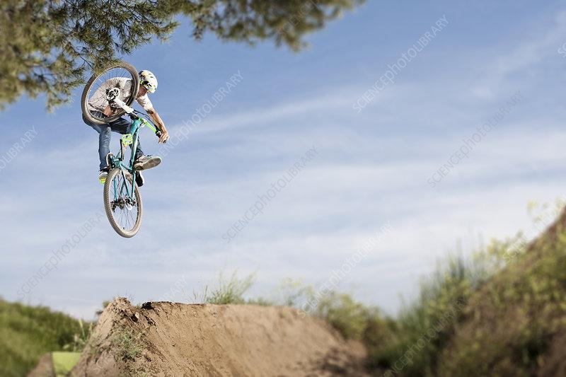 Dirt biker doing tricks during jump