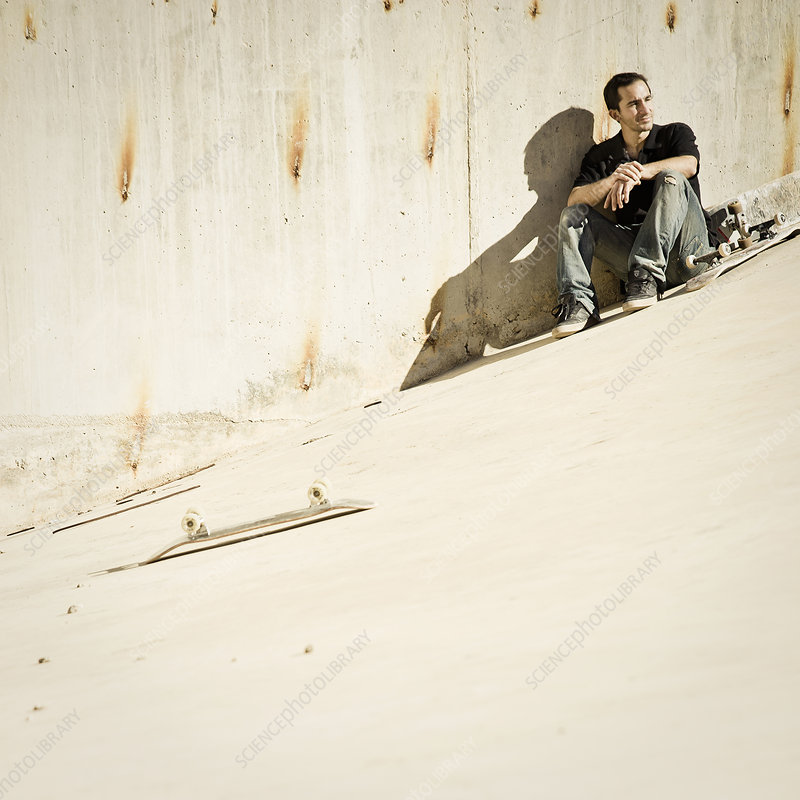 Skateboarder sitting on concrete slope