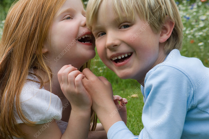 Children whispering in field of flowers