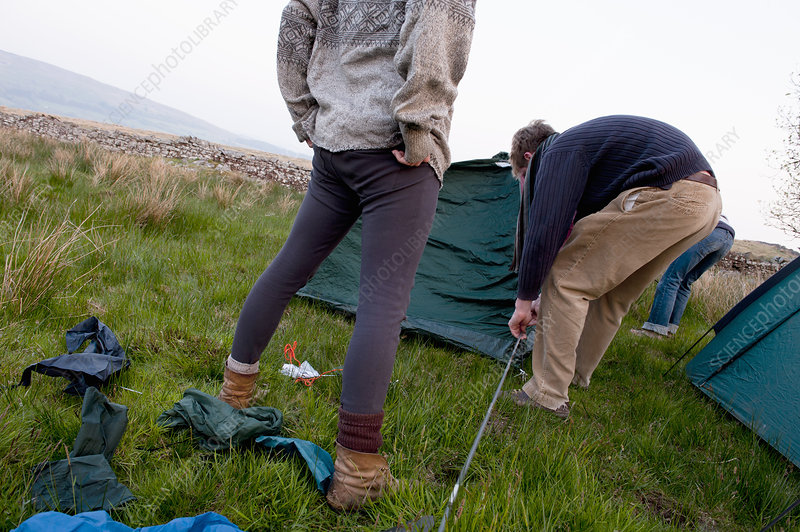 Couple pitching a tent at campsite