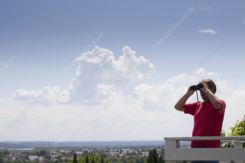 Older man using binoculars on roof