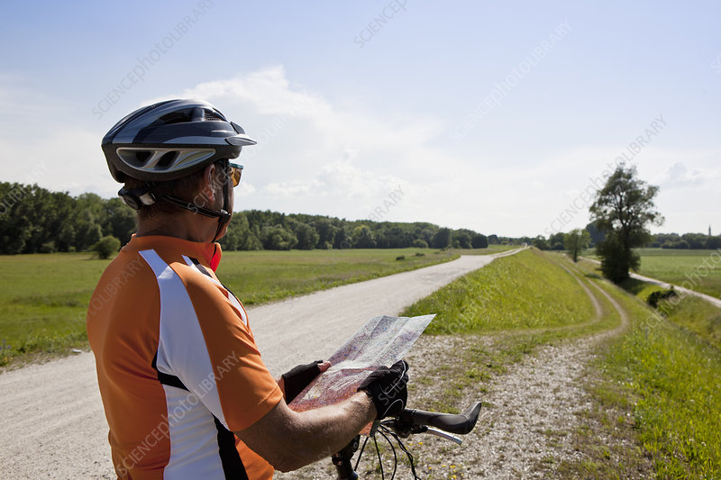 Biker reading map on rural road