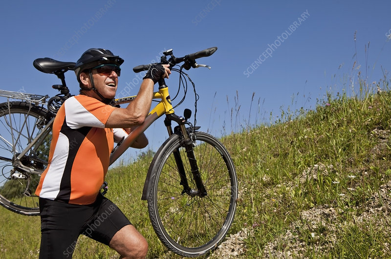Man carrying bicycle on grassy hillside