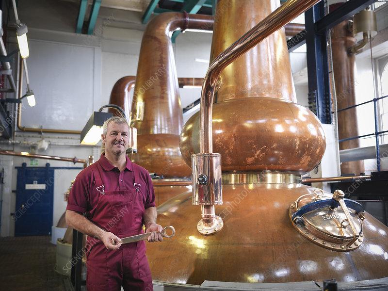 Worker with stills in distillery