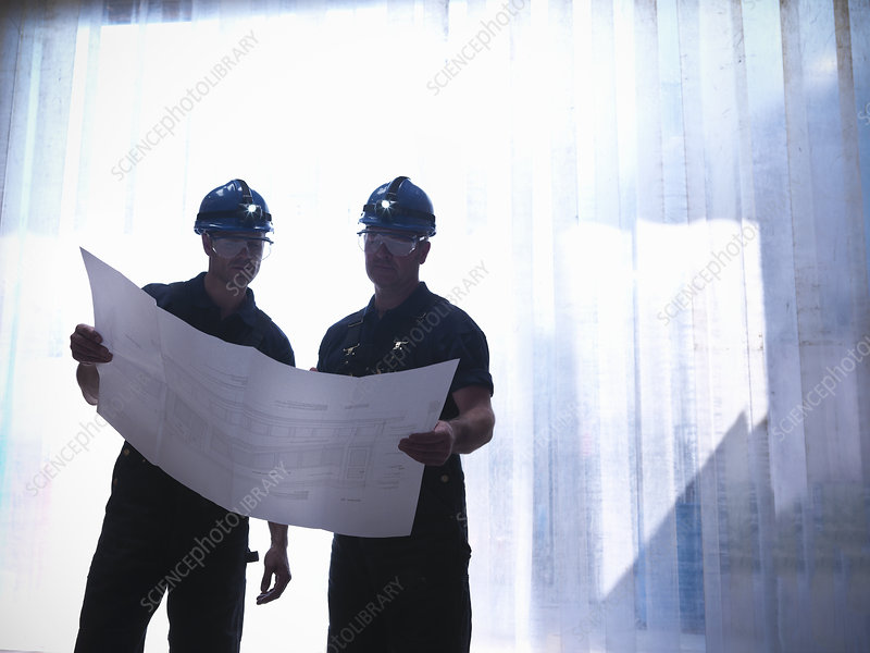 Workers examining blueprints together