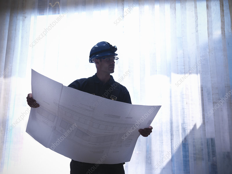 Worker examining blueprints