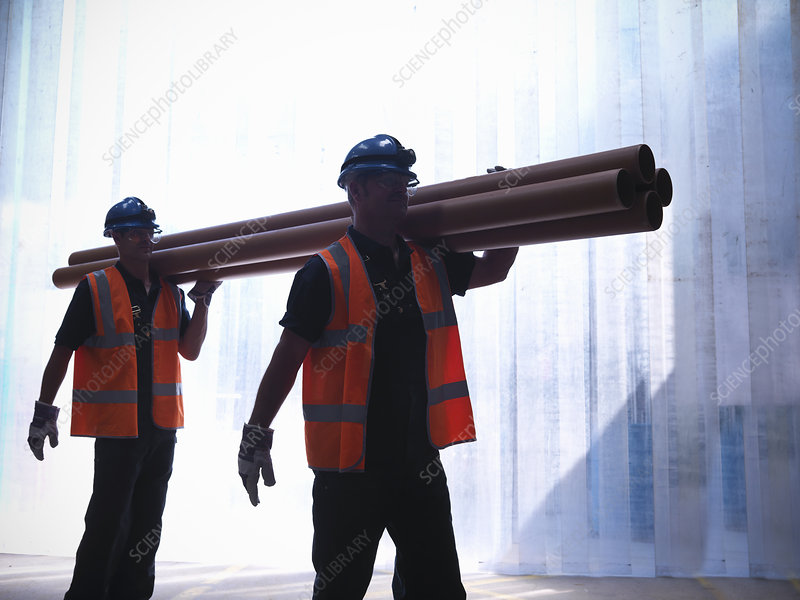 Workers carrying pipes together