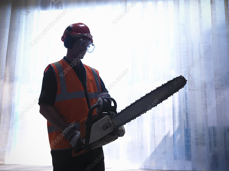 Worker holding chainsaw