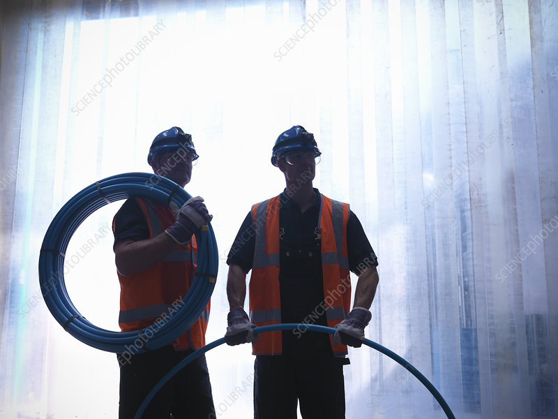 Workers holding water pipes