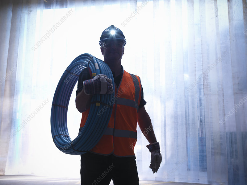 Worker carrying water pipes
