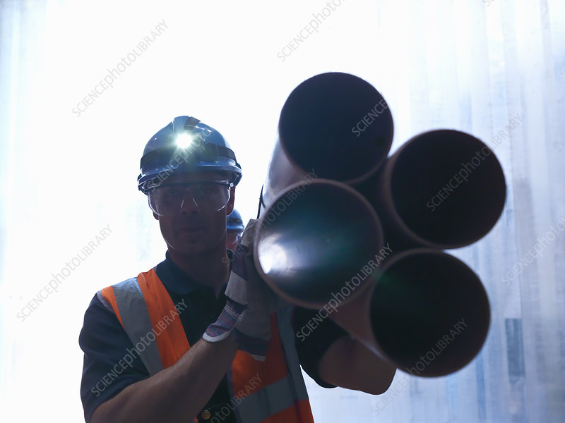 Worker carrying pipes