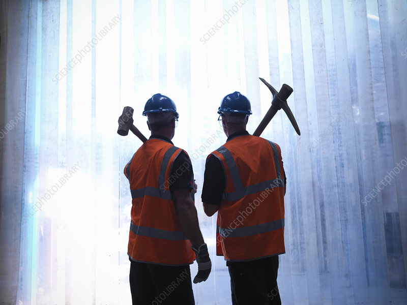 Workers holding pickax and hammer