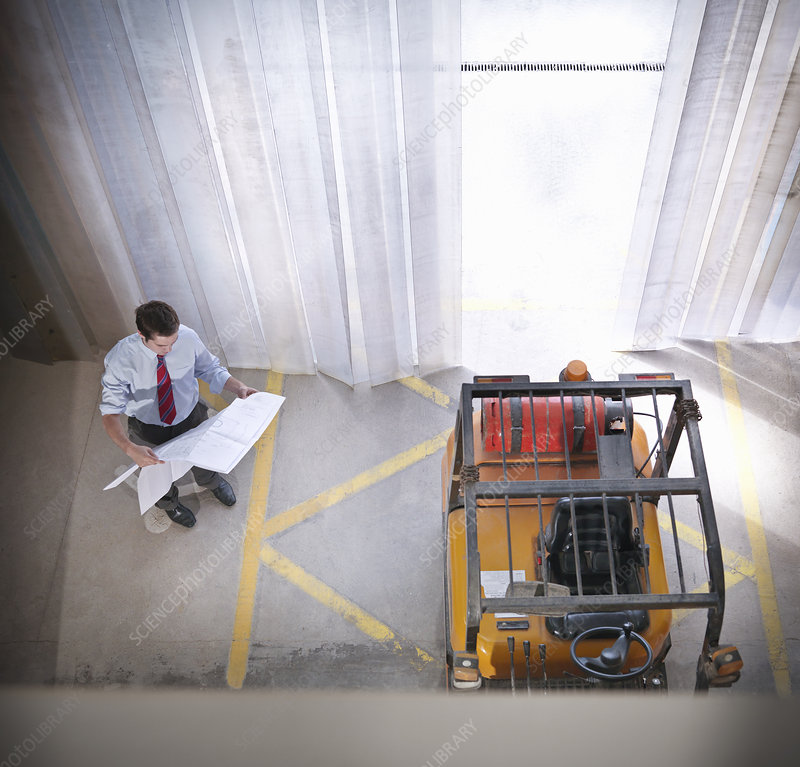Businessman reading blueprints on site