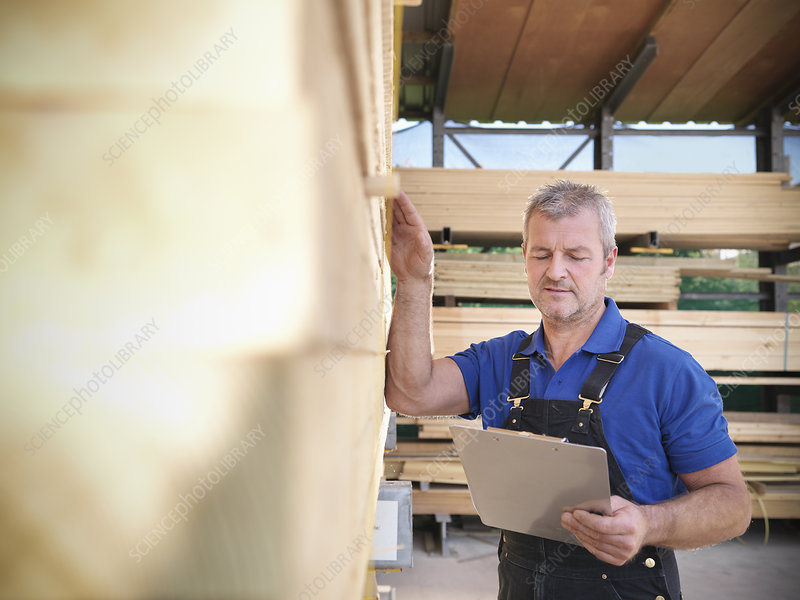 Worker checking wooden planks in joinery